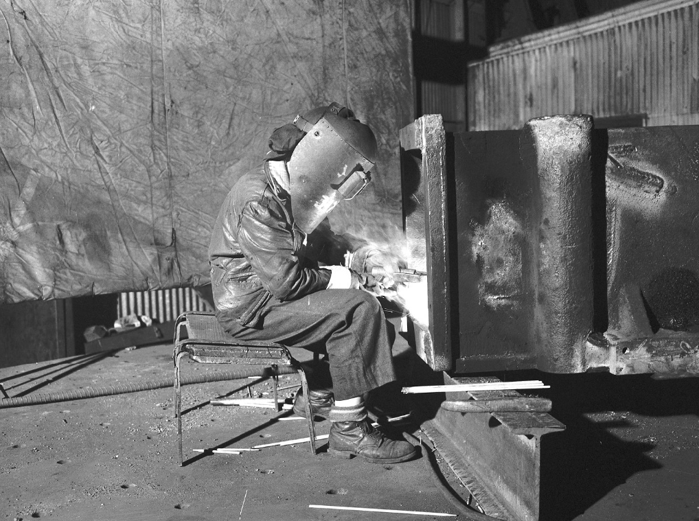 A woman sits on a stool wearing a protective mask while welding a metal beam