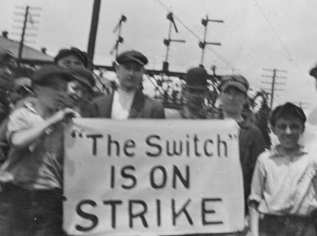 """Men and boys stand around a sign reading """"'The Switch' is on strike"""""""