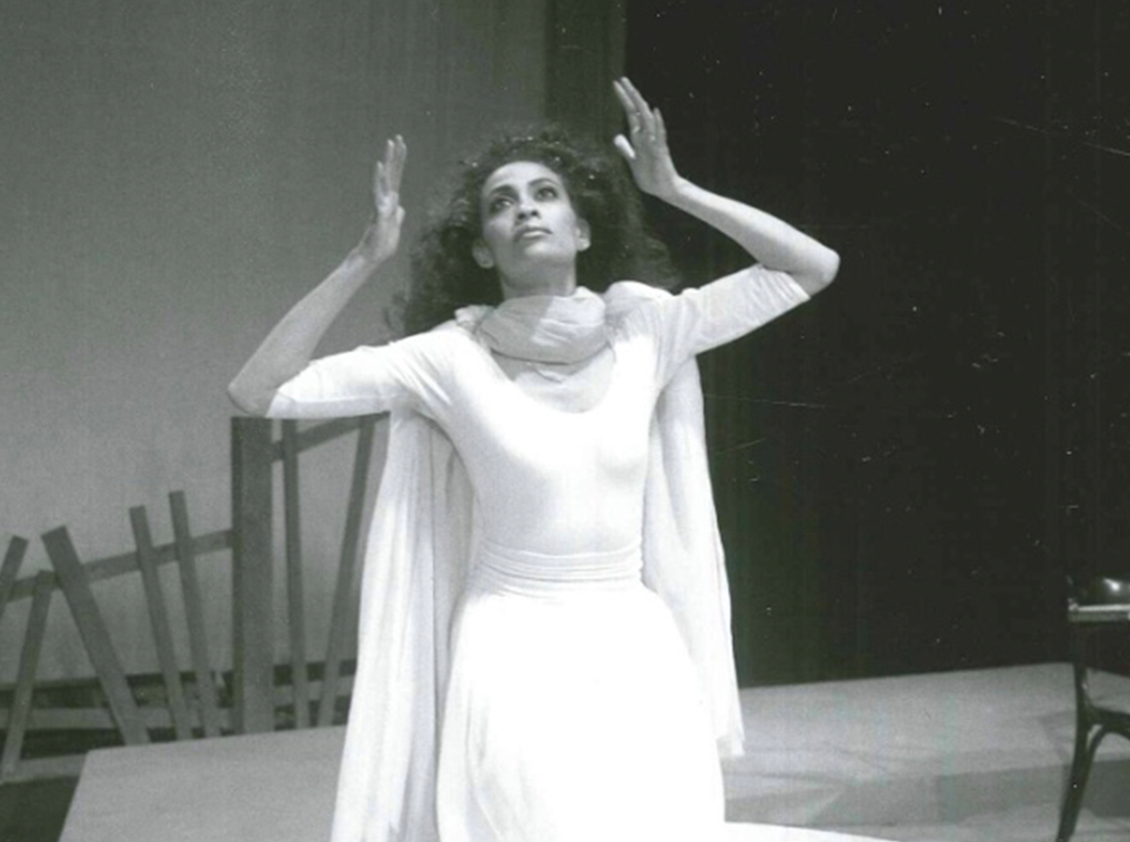 A woman dressed in white kneels on a pedestal on a stage and raises her hands to frame her head