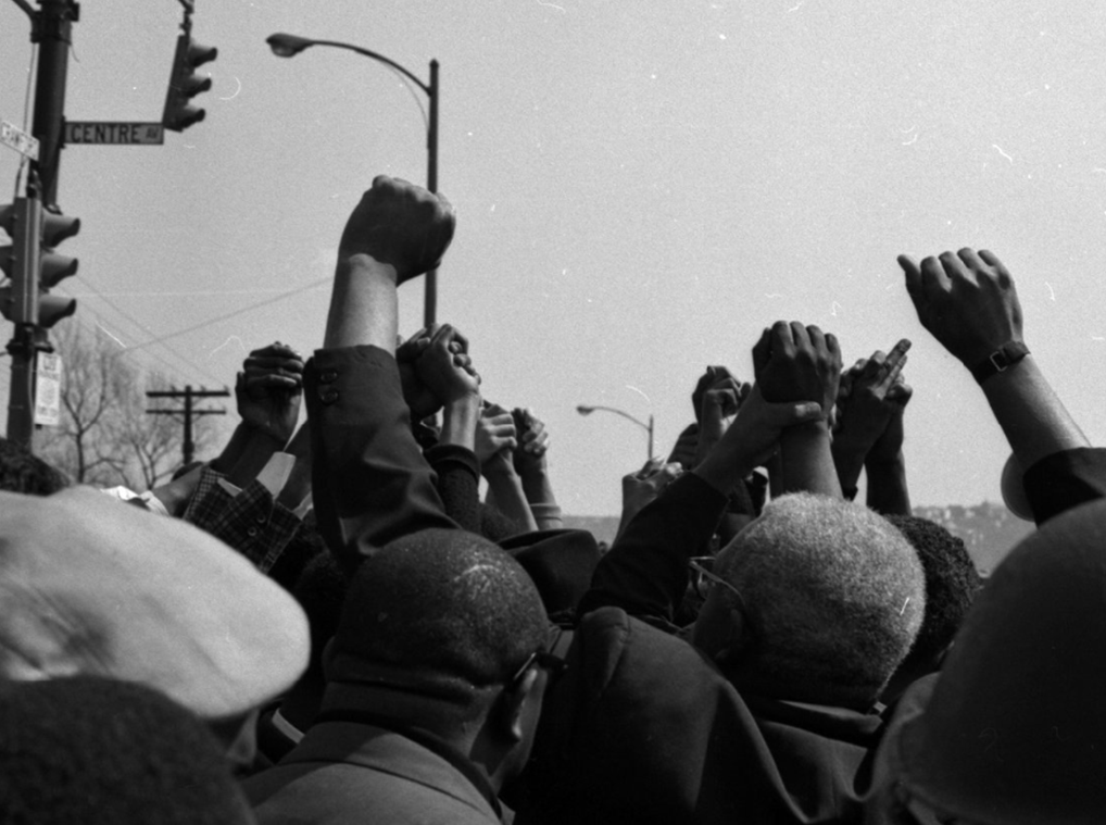 Men stand with their fists raised in a crowd of people.