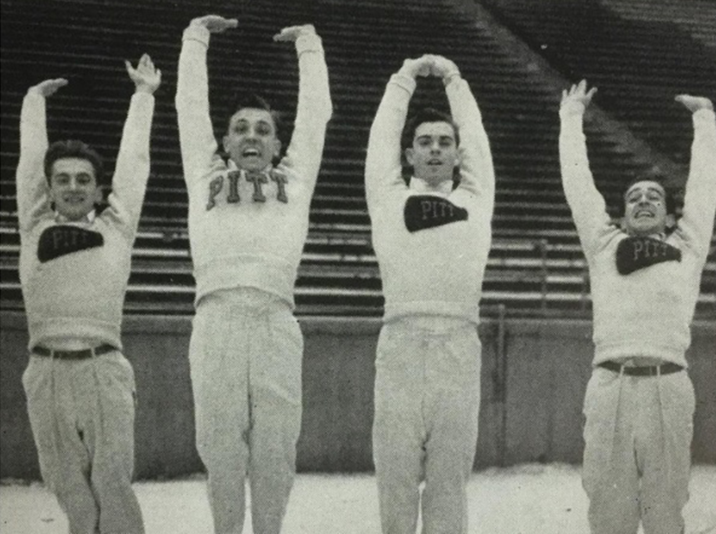 Four male cheerleaders wearing Pitt sweaters jump with their arms raised