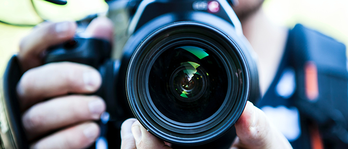 A person holding a camera with the lens facing towards the viewer