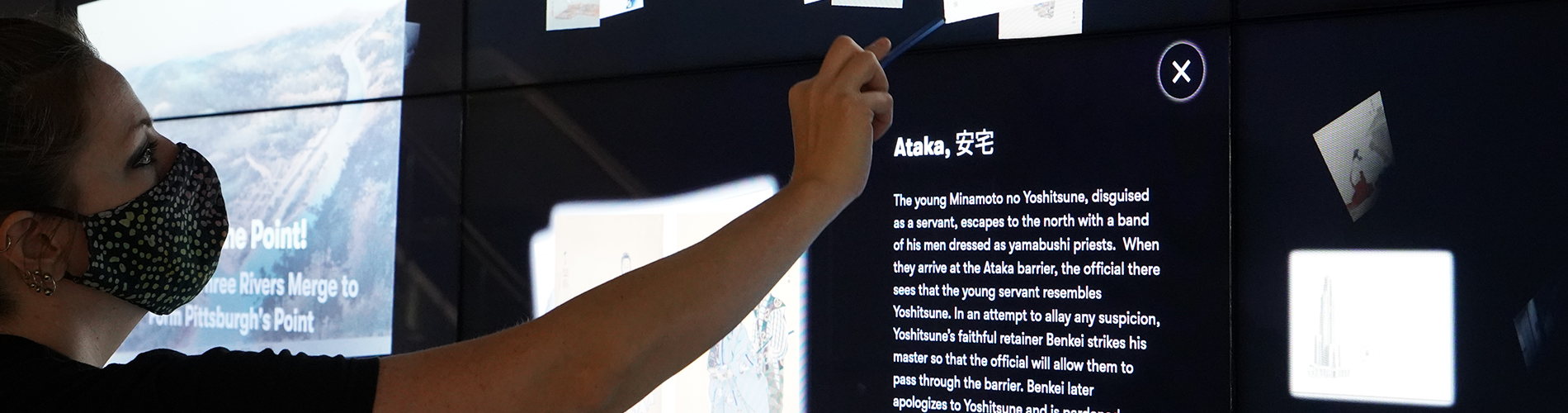A woman using a stylus to on the Interactive Wall