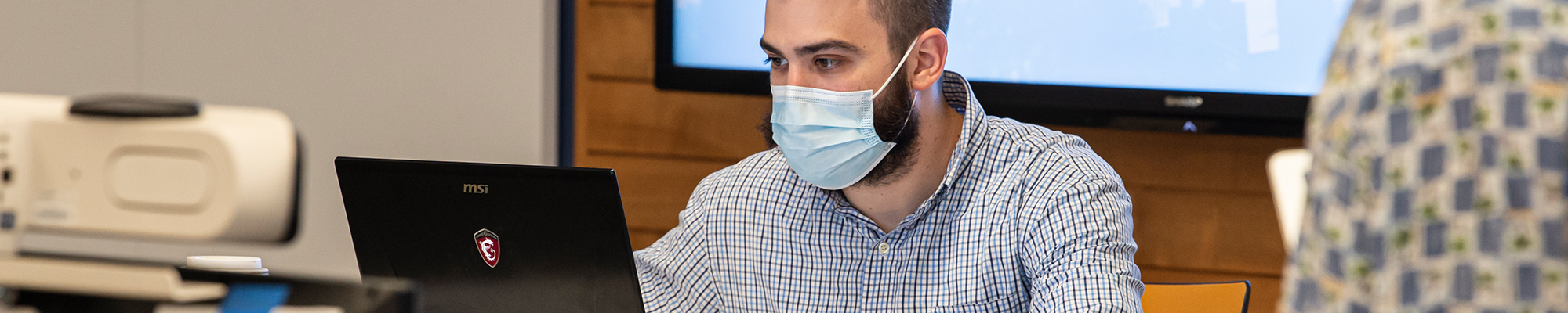 Man working on a computer with a face mask on